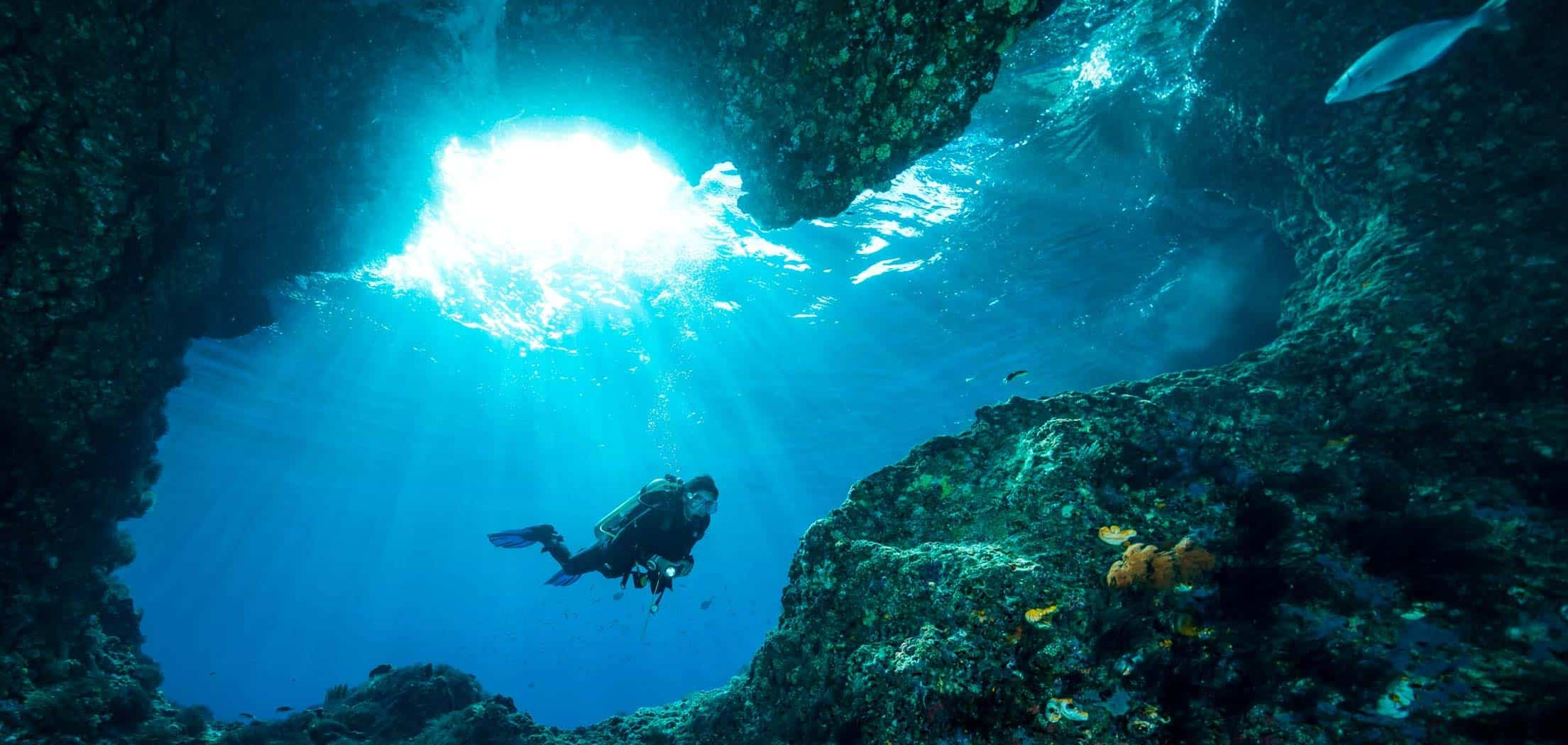 A scuba diver woman swimming in an underwater cave